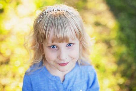 Portrait of a cute blue-eyed girl in a blue shirt