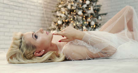 Attractive young woman lies on the floor by the christmas tree
