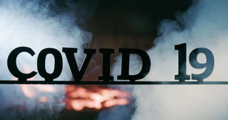 The word Covid-19 in clouds of fog and fire in the background 免版税图像