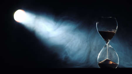 Bright beam of the spotlight illuminates the hourglass, in the light of the swirling mist