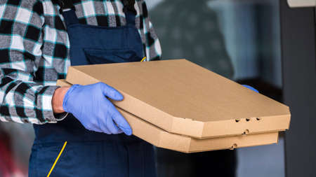 Safe delivery of the pizza, the courier holds the box in protective gloves. Side view 免版税图像