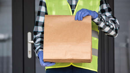 A courier in gloves holds a bag of food. Delivery of food during quarantine and self-isolation 免版税图像