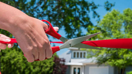 Cut the red ribbon in front of the new house. Housewarming and home buying concept 免版税图像