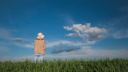 A woman stands on a green meadow against a beautiful blue sky with clouds
