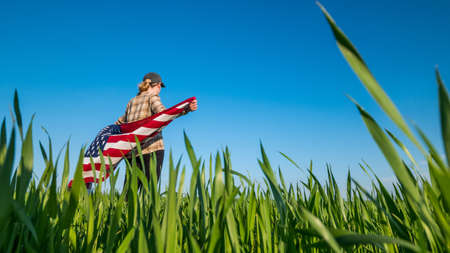 A woman with a U.S. flag on her shoulders stands on a picturesque green meadow