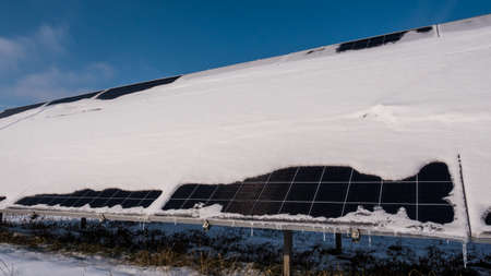 A layer of snow on the panels of a solar power plant. Green energy problems and weather dependence