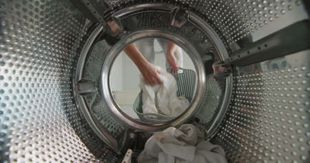 A woman puts white laundry in the washing machine