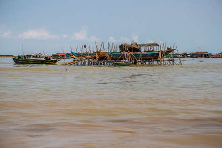 Fishermens dwellings on the water at Tonle Sap Lake in Cambodia. Near their boats 免版税图像