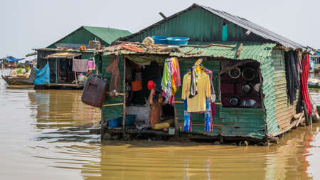 Cambodia, Tonle Sap Lake, February 2012: A child bathes in his hut on the water. Housing and life of Khmer fishermen