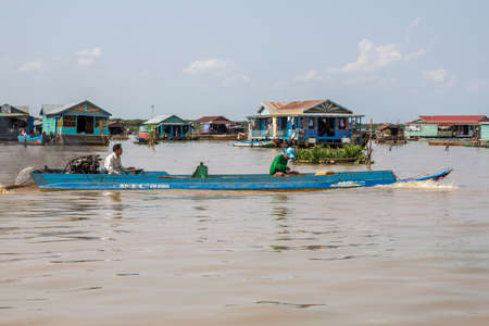 Cambodia, Tonle Sap Lake, February 2012: Fishermen sail on a boat against the backdrop of huts on the water. Life of the Khmers living on the lake 新闻类图片