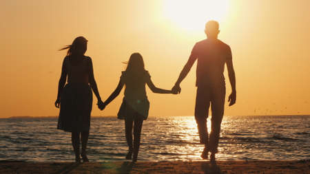 Family with a child goes to the sea at sunset