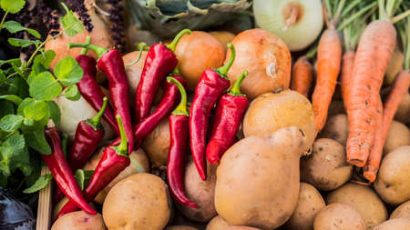 Potatoes and peppers - fresh vegetables on a farmers market counter Imagens