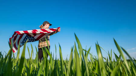 Wind swayes U.S. flag in the hands of a woman standing on a green wheat field