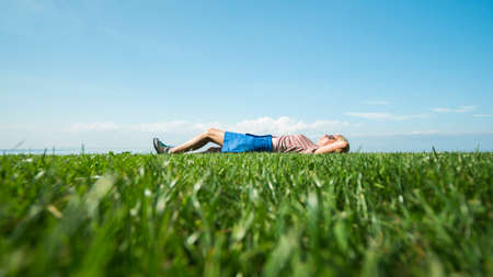 A young woman enjoys warmth and summer, lying on the green grass against the blue sky