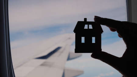 Silhouette of a female hand with a small house. Against the background of the planes window. Concept - homesickness