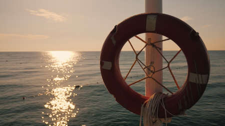 Lifebuoy hanging on the background of the sea at sunrise. Morning at the sea Imagens