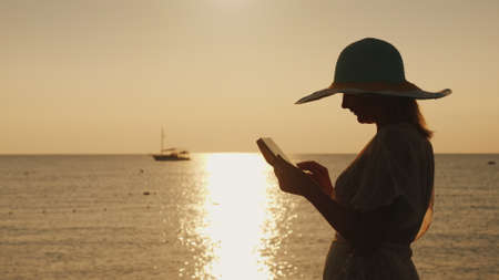 Silhouettes a young woman in a wide-brimmed hat that uses a tablet against the backdrop of a beautiful sunrise on the seashore