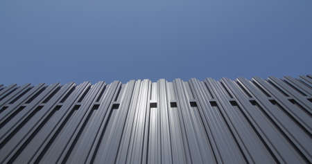 Grey metal shuttle fence against blue sky Imagens