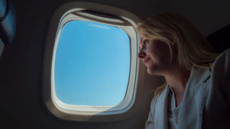 Young woman traveling in an airplane, looking at the sky through the porthole 版權商用圖片