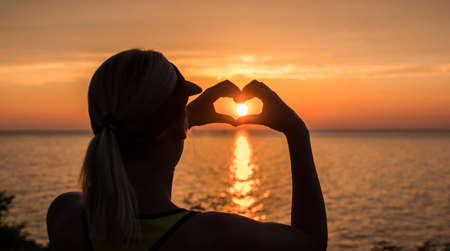 A woman looks at the sea where the sun sets, shows a heart-shaped figure