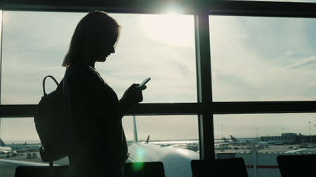 Always online. Silhouette of a woman using a smartphone in an airport terminal near a large window 写真素材