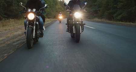 A group of bikers drives along the highway, in the frame you can see the wheels and headlights