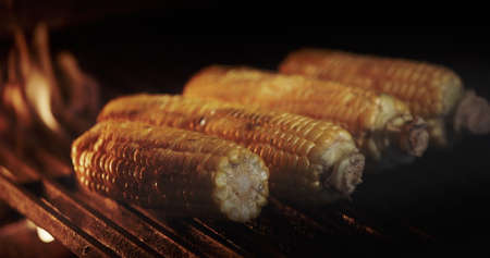 Delicious cobs of corn are fried on a hot grill grill