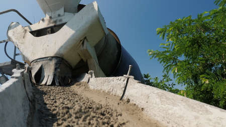 Concrete flows from the concrete mixer through the trough, concrete delivery and construction work 写真素材