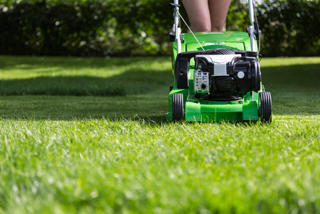 mower: Young woman mowing the lawn.