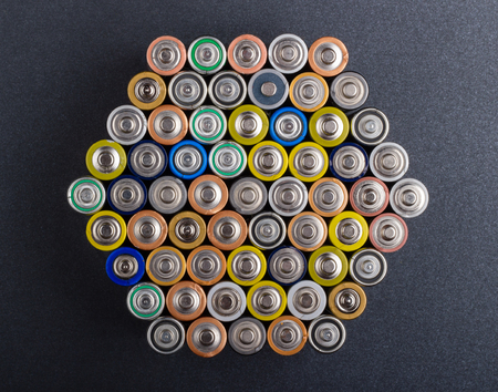 Battery AA texture blurred in a row. Rows of batteries, top view. Multicolored batteries AA, cell row hexagon organized