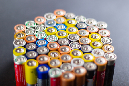 Battery AA texture blurred in a row. Defocused rows of batteries, perspective view. Multicolored batteries AA, cell row hexagon organized
