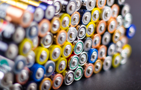 Battery AA texture background in a pile. Organized battery AA rows. Perspective view AA batteries texture.