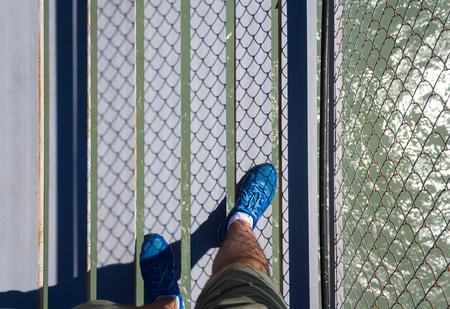 A man walks through a suspended metal bridge across the river. Close-up Stock Photo