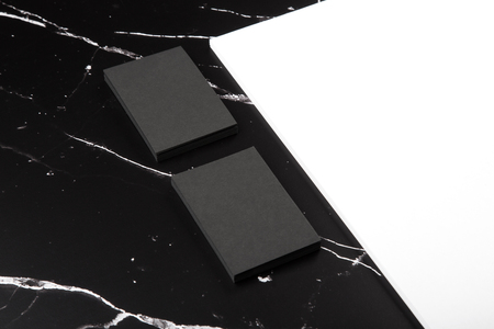Photo of branding identity mock up on marble. Template isolated on marble background. Black business cards and white letterhead on black marble.