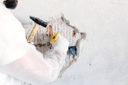 Worker removes plaster from a brick wall with a chisel.