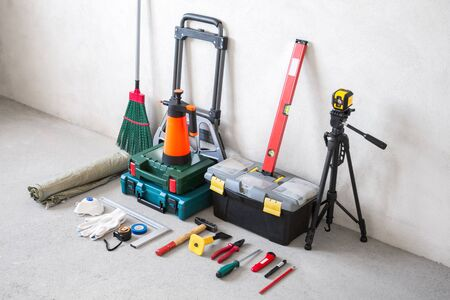 Repair tools are neatly laid out on the concrete floor in unfinished apartment. The set includes power tools, hand tools and a trolley for their transportation.