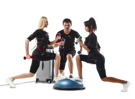 Group of fitness athletes in electrical muscular stimulation suits doing lunge exercise with dumbbells. Standing on bosu ball. Isolated on white background. 写真素材