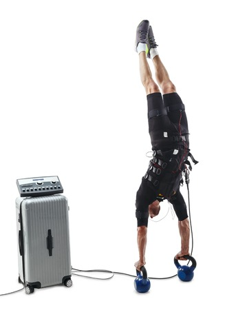 Fitness athlete in electrical muscular stimulation suit doing a vertical handstand upside down on dumbbells. Isolated on white background.