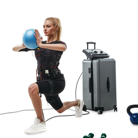Blonde EMS fitness woman in full electrical muscular stimulation suit doing lunge exercise with ball. Kettlebells and dumbbells around her. Isolated on white background.