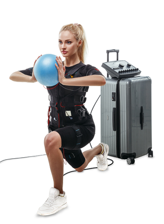 Beautiful blonde EMS fitness woman in full electrical muscular stimulation suit doing lunge exercise with ball. Isolated on white background.