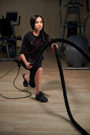 Electrical muscular stimulation fitness brunette woman in full ems suit doing crossfit training using rope. Glowing effect. Gothic style.