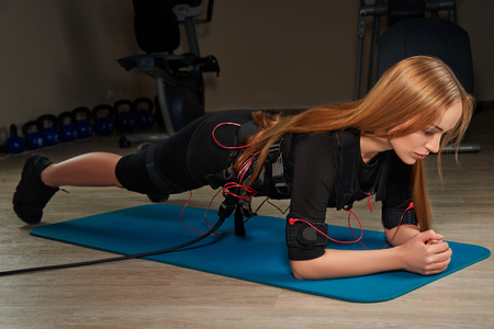 Blonde girl in Electrical Muscular Stimulation suits doing plank exercise on sports mat. Glowing effect. Gothic style. EMS. Workout.