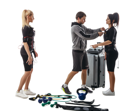 Trainer helps fitness women to set full electrical muscular stimulation suits. Various sport gear like kettlebells, dumbbells, belts and expanders around them. Studio photo isolated on white background. Stock Photo
