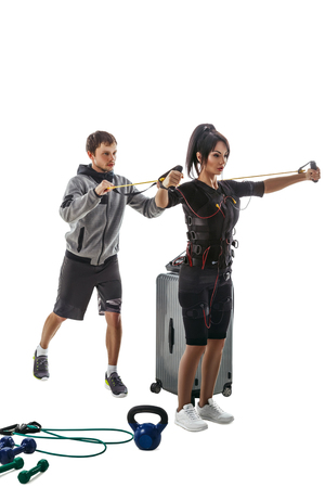 Electrical muscular stimulation fitness woman in full ems suit. Trainer helps her. Studio photo isolated on white background.