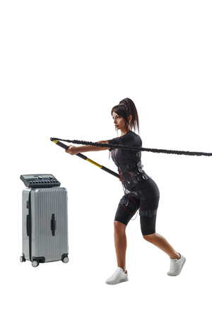 EMS fitness woman in full electrical muscular stimulation suit doing lunge exercise with a bar on flexible band. Studio shot isolated on white background.