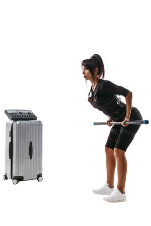 EMS fitness woman in full electrical muscular stimulation suit doing exercise with fitness bar. Studio shot isolated on white background. Stock Photo