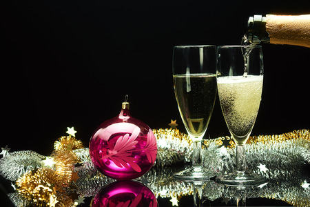Champagne pouring into glasses and christmas new year decorations with ball isolated on black background
