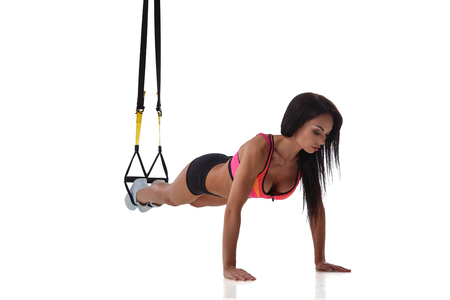 Woman exercising with suspension straps isolated on white background. 版權商用圖片