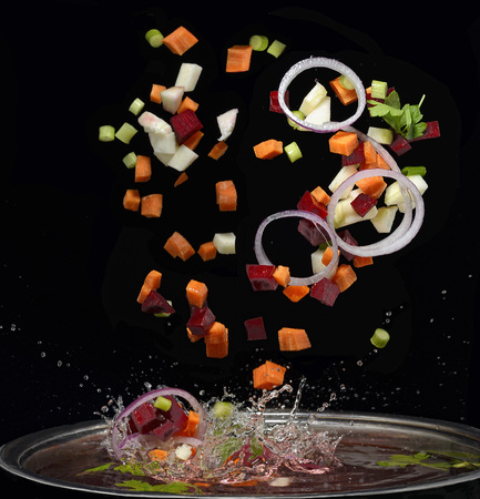 Cut vegetables splash in water soup cooking concept isolated on black background