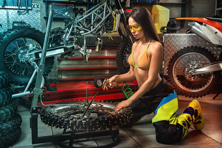 Sexy girl in garage with motorcycles checking tyre pressure with manometer Stockfoto
